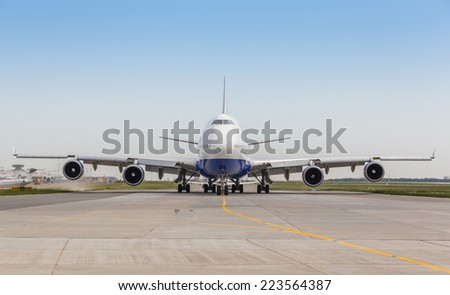 White jet airplane on the runway on a sunny day on blue sky background - stock photo