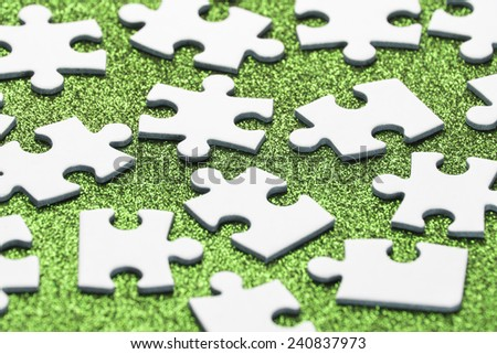 White jigsaw puzzle on green background  - stock photo
