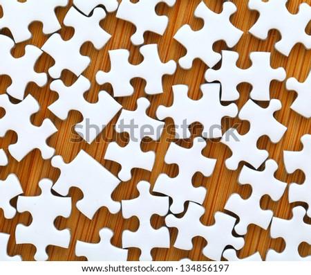 white jigsaw puzzle on wooden background - stock photo