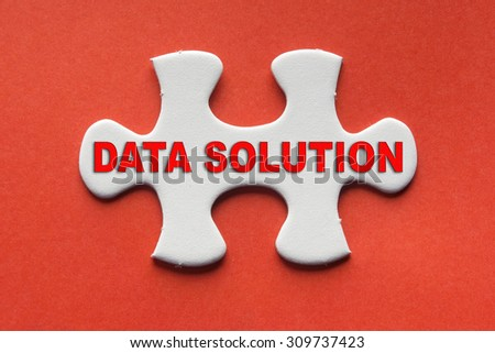 White jigsaw puzzle with a written word data solution on a red background. - stock photo