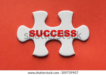 White jigsaw puzzle with a written word success on a red background. - stock photo