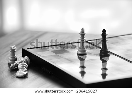 White king facing black king on chess board with  lost pieces beside, business concept - stock photo