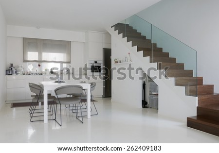 white kitchen and dining room with white epoxy floor and wooden stairs - stock photo