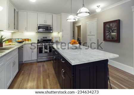 White Kitchen in Modern Home with white Marble counter tops wooden floor and all new appliances. - stock photo