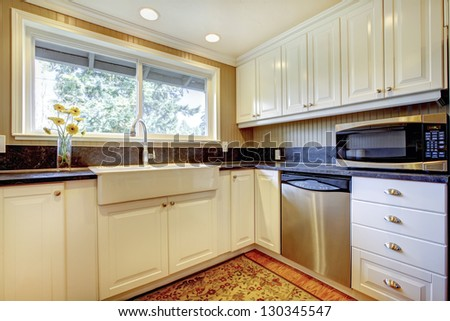 White kitchen interior with large sink and window. - stock photo