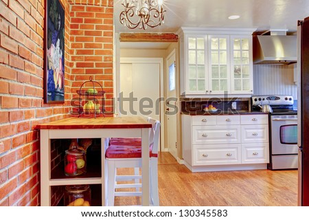 White kitchen with brick wall, hardwood and stainless steal stove with breakfast table. - stock photo