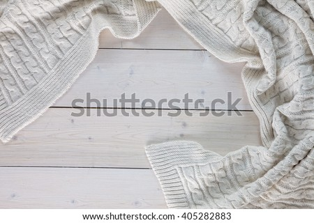 white knitted blanket. spit on the blanket. lying on white wooden floor in soft folds. in the centre of the empty place of inscription, text. - stock photo