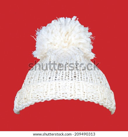 White knitted wool hat with sequins isolated on red - stock photo