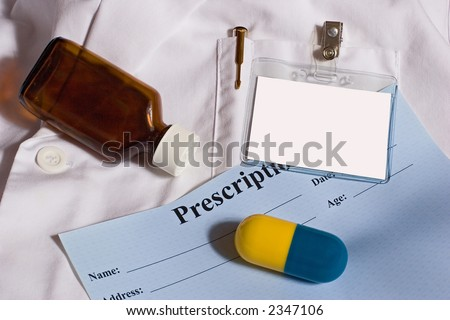 White labcoat for a pharmacist.  Includes blank name badge, large capsule, and amber medicine bottle. - stock photo