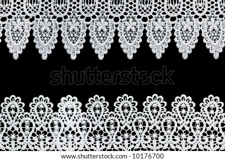 White lace forms a delicate border against black background. - stock photo