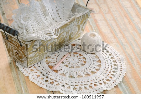 white lace in vintage basket on a wooden table  - stock photo