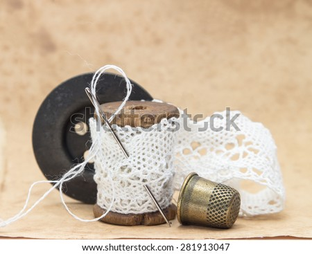 white lace ribbon, wound on a wooden bobbin with needle for sewing, a large black wooden button and a metal thimble, vintage, vintage accessories - stock photo