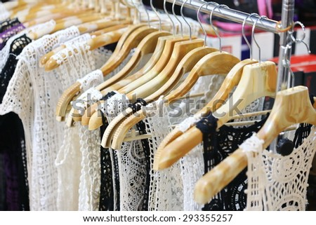 white lace women vest, ladies garments, shop ,looking through new clothes during shopping,Colorful women's dresses on wood hangers in a retail shop. Fashion and shopping business concept.  - stock photo
