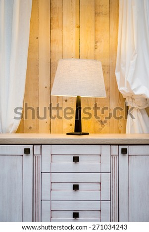 White lamp on the wardrobe with raw wooden wall in the background - stock photo