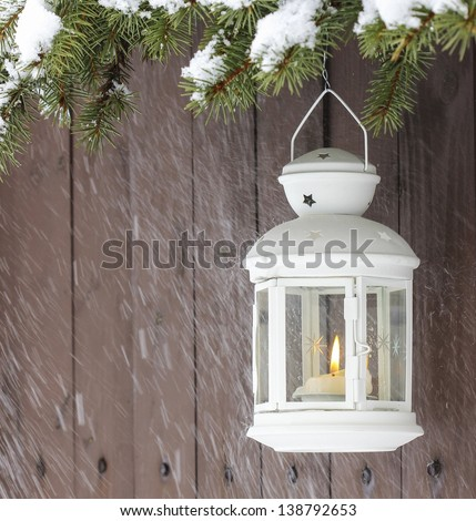 White lantern hanging on a fir branch. Selective focus. - stock photo