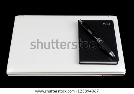 White laptop with pocket calendar and pen isolated on black background - stock photo