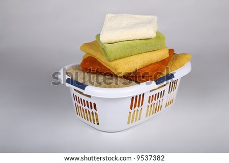 White Laundry Basket with fresh clean towels - stock photo