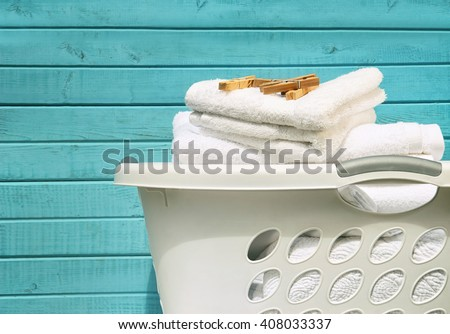 White laundry basket with towels and clothes pins - stock photo