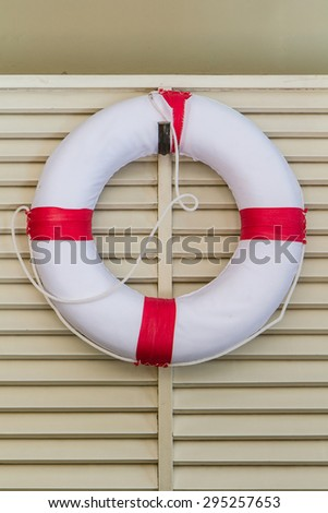 White life-buoy hanging on wooden wall - stock photo