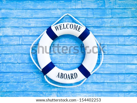 White Life buoy with welcome aboard on blue wall - stock photo