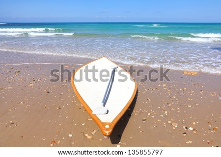 White lifeguard surf board on the beach - stock photo