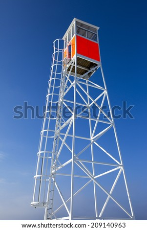 White lifeguard tower and strong blue heaven in background - stock photo