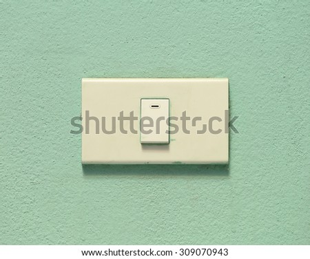 White light switch on green cement wall  - stock photo