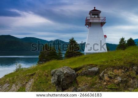 White lighthouse on the coast of Newfoundland, Canada - stock photo