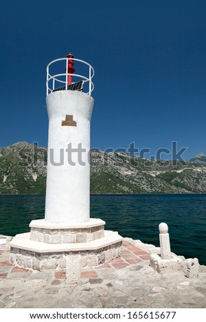 White lighthouse tower on the island of Lady of the Rocks. Bay of Kotor, Montenegro - stock photo