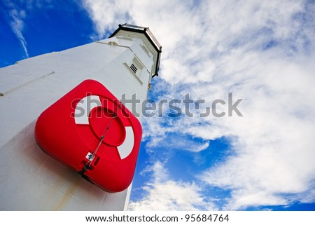 White lighthouse with a red life preserver against a cloudy blue sky on a bright winter morning. Photo taken in Anstruther, Scotland. - stock photo