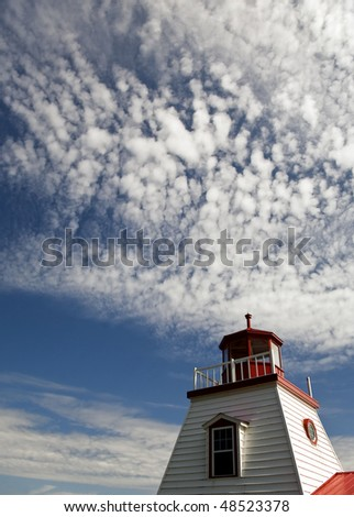 White Lighthouse With Summer Clouds Overhead - stock photo