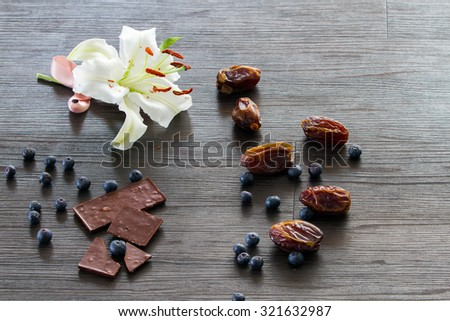 White lily with pink ribbon and dry dates, chocolate and blueberries - stock photo
