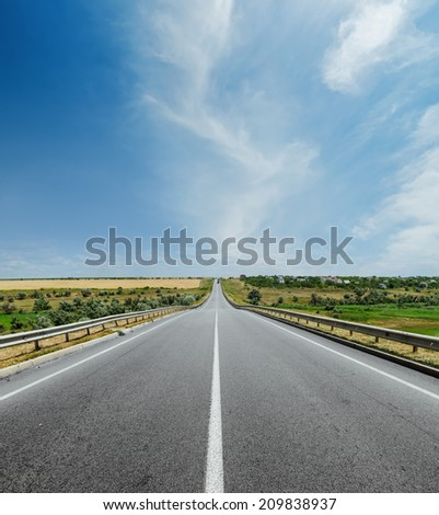 white line on asphalt road and clouds in sky over it - stock photo