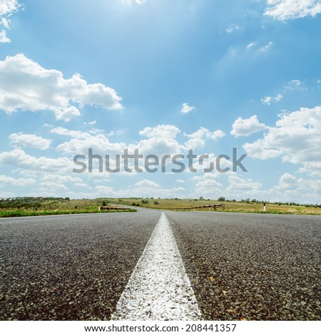 white line on asphalt road under sky with sun and clouds - stock photo