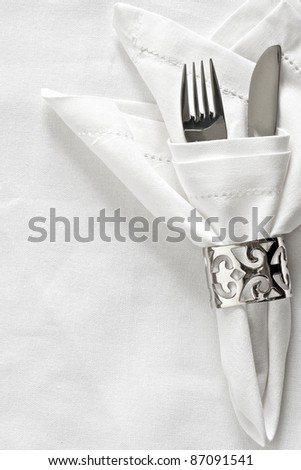 White linen napkin and silver napkin ring with cutlery - stock photo