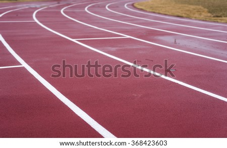White lines mark the lanes on a wet worn red running track. - stock photo