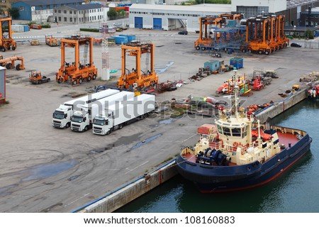 White lorries and orange loaders stand in port. Ship is close to quay. - stock photo