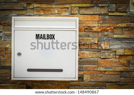White mail box hang on the rock background - stock photo
