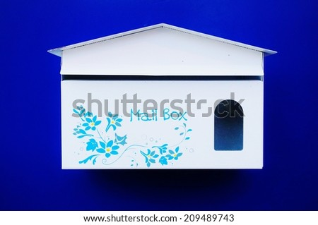 White mailbox on blue background with blue and yellow flowers - stock photo