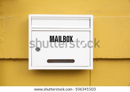 White Mailbox on the yellow wall - stock photo