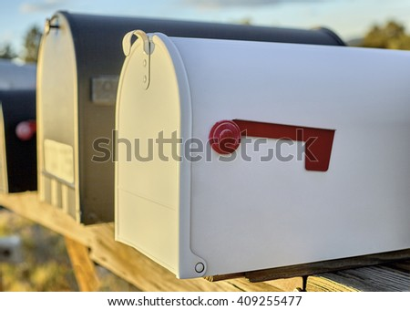 White Mailbox with a red flag in the down position with shallow depth of field - stock photo