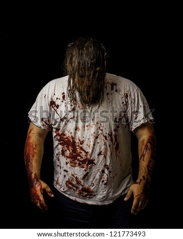 white male wearing a white shirt covered in blood with his hair covering his face. - stock photo