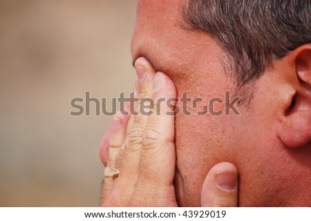 white man expressing tiredness and despair with his hands on his face - stock photo