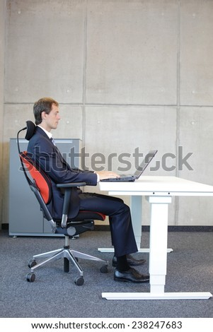 white man in suit in correct sitting position at workstation in office - stock photo