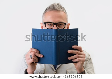White man smile and hides his face behind a book. Studio portrait - stock photo