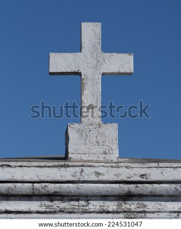 white marble cross on tombstone against deep blue sky - stock photo