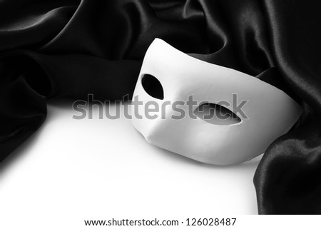 White mask and black silk fabric, isolated on white - stock photo