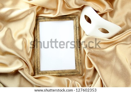 White mask and empty frame on golden silk fabric - stock photo