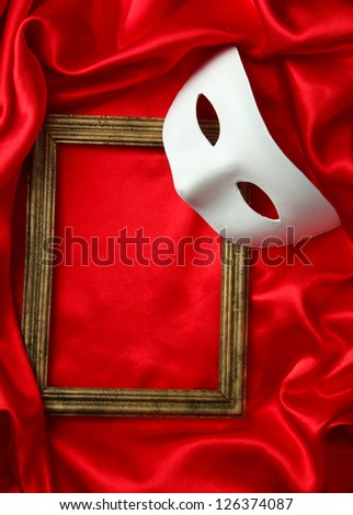White mask and empty frame on red silk fabric - stock photo