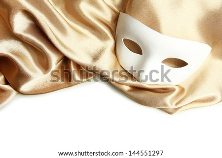 White mask and golden silk fabric, isolated on white - stock photo